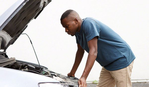 Side portrait of young african man looking under the hood of car