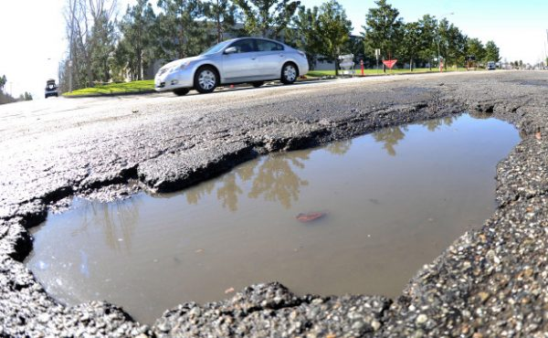 A vehicle drives past a rain filled pothole along Francis Street in Ontario Friday January 27, 2017.   (Will Lester-SCNG/Inland Valley Daily Bulletin)